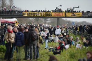 "French protesters hold a banner reading ""An airport in Notre-Dame-des-Landes, never!"" as they block a highway in Le Temple-de-Bretagne during a demonstration against a controversial airport project near Nantes on February 27, 2016. Protesters have been engaged in a 15-year legal battle to block the construction of a major new airport on swampland outside the western city of Nantes. Approved in 2008, the 580-million-euro (747 million USD) project had been due to start in 2014 but has been repeatedly delayed due to fierce opposition by environmental protesters. / AFP / JEAN-SEBASTIEN EVRARD"