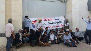 Sit-in des employés protestataires devant les bureaux de Total à Sana'a au Yémen. Sur la banderole, on peut lire : «Ils ont commencé par le pillage des ressources du Yemen et ils finissent par le pillage des droits des employés»