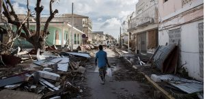 A man walks on a street covered in debris after hurricane Irma hurricane passed on the French island of Saint-Martin, near Marigot on September 8, 2017. Officials on the island of Guadeloupe, where French aid efforts are being coordinated, suspended boat crossings to the hardest-hit territories of St Martin and St Barts where 11 people have died. Two days after Hurricane Irma swept over the eastern Caribbean, killing at least 17 people and devastating thousands of homes, some islands braced for a second battering from Hurricane Jose this weekend. / AFP PHOTO / Martin BUREAU